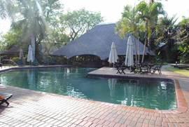 hoofdzwembad met verzonken bar en terras met zitjes en zonnebedden