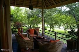 lounge-set op de veranda met uitzicht over de tuin en vijvers