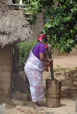 Vrouw die pinda's stampt in Township