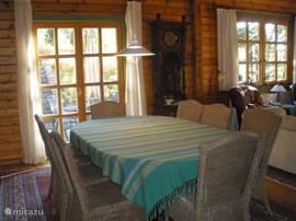 Eetkamer met grote 8 persoonstafel, uitbreidbaar tot 12. Openslaande deuren naar het terras.