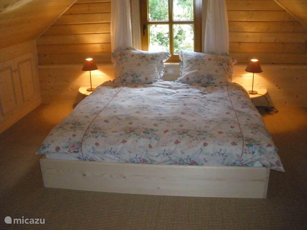 Het knusse slaapgedeelte van de grote slaapkamer boven met een apart zitgedeelte, een kinderbedje en een commode en een eigen badkamer.