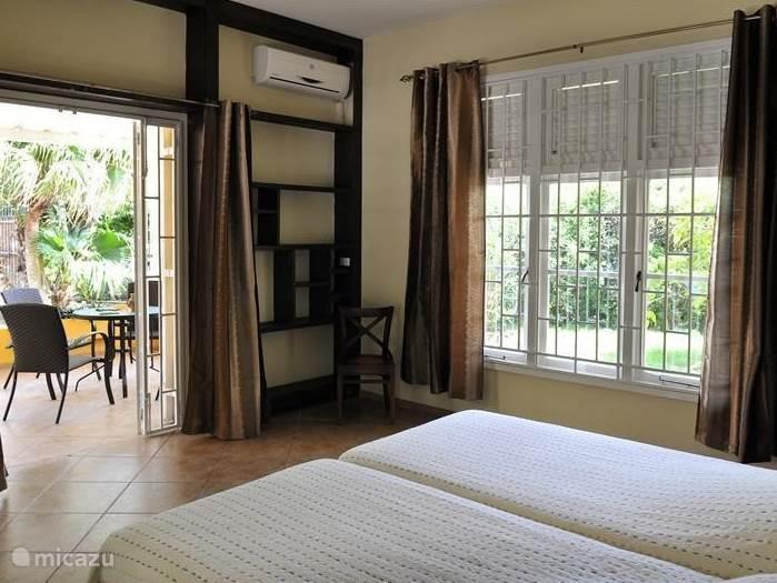 Slaapkamer met openslaande deuren naar terras met zitje.