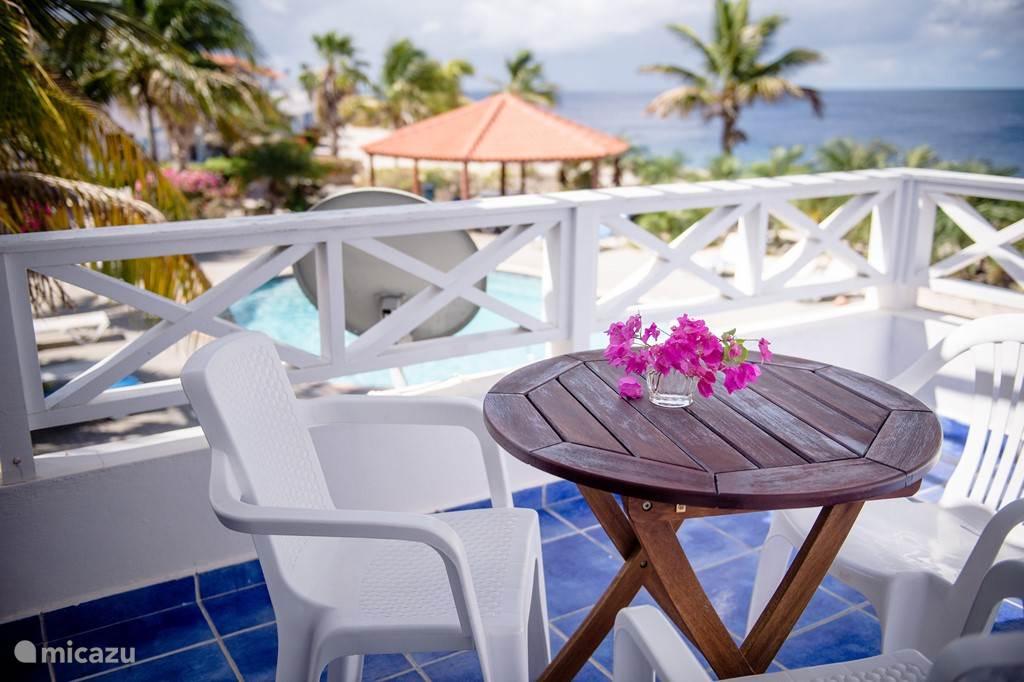 Zicht vanaf het balkon op het zwembad en de zee