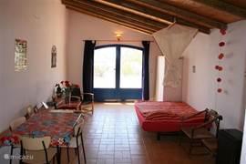 De binnenzijde van het gastenverblijf vanuit de open keuken bekeken. Door de openslaande grote deuren komt u op het grote terras (zie andere foto).