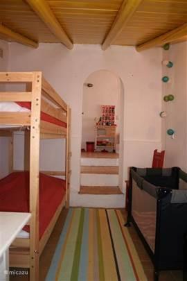 De slaapkamer in het gastenverblijf met stapelbed en kinderbedje. Door de poort heen kijkt u naar de open keuken.