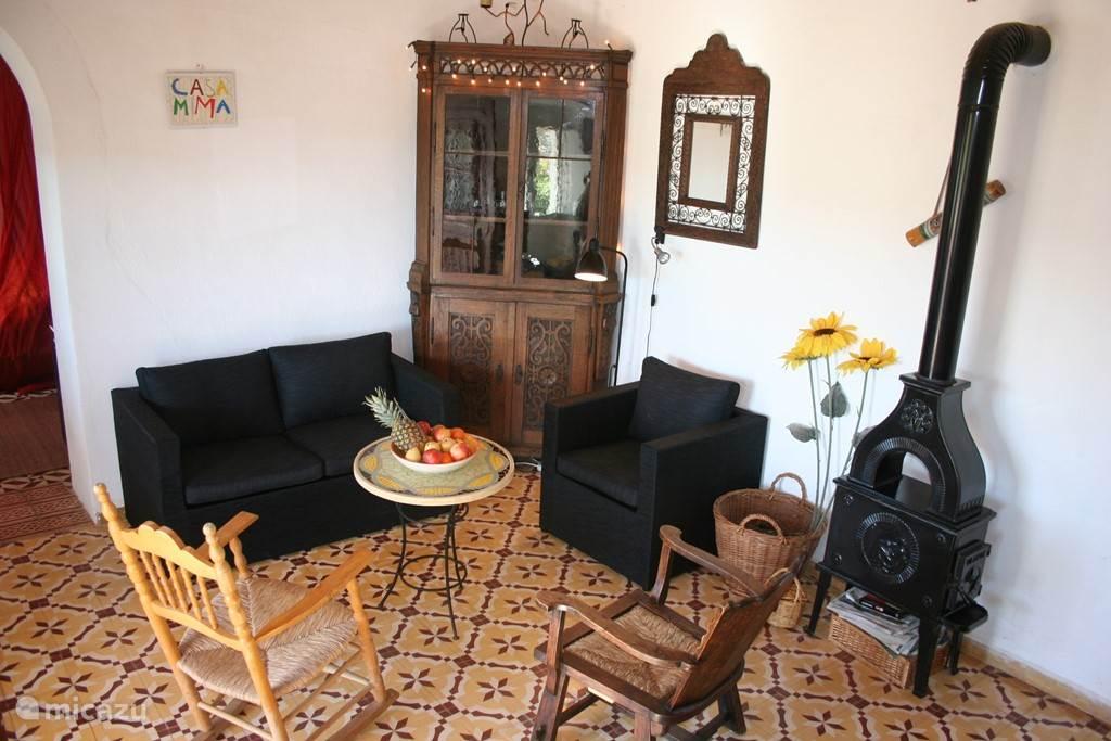 De zithoek in de huiskamer, compleet met houtkachel. Maar die heeft u alleen in de winter nodig. Op de grond de originele Portugese vloertegels. Links de doorgang naar de slaapkamers.
