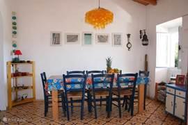 De eethoek in de huiskamer. Rechts een van de ramen met uitzicht op het terras en de vallei. Links de doorgang naar de keuken. Op de grond de originele Portugese vloertegels.