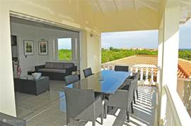 Porch with large dining table and chairs adjacent to the living room. From the terrace on the porch you on all sides overlooking the Caribbean Sea. A perfect place to enjoy the sea or the sunset. There is often a nice breeze blowing.