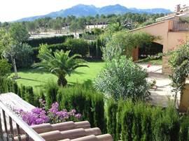 Vanaf het terras heeft u dit gezicht op de gemeenschappelijke tuin met de villa's in een halve cirkel er omheen. Links is het gemeenschappelijke zwembad.