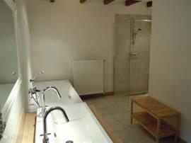 Heerlijk grote badkamer, zicht op de wastafel, ligbad en inloopdouche.