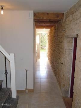 In de hal zijn de oude stenen zichtbaar; naast de trap is er een ruimte als garderobe ingericht.