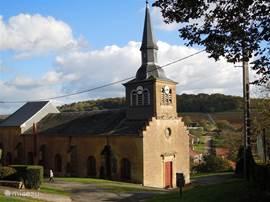 Uitzicht op de kerk, het dorp, de velden en de heuvels.