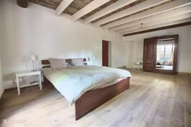 Een grote slaapkamer (25 m2) met openslaande deuren die via een trap naar de tuin en het terras leiden