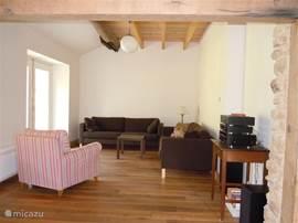 Een deel van de woonkamer met openslaande deuren naar het terras en de tuin. Vanuit deze woonkamer heeft u een mooi gezicht op de tuin, het andere deel van de woonkamer en de houtkachel.
