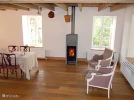 Eetkamer met deel van de eettafel, deze staat in het verlengde van de keuken. Ook staan in dit deel twee lekkere fauteuils om warm bij de houtkachel te zitten.