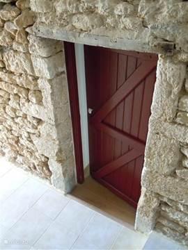 Een stoere rode boerendeur als ingang van de slaapkamer.