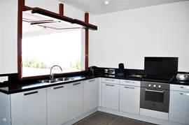 De keuken met nespresso, magnetron, oven, vaatwasmachine. In de achterliggende bijkeuken staat de wasmachine.