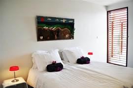 Slaapkamer 2 met shutters en toegang tot de badkamer.