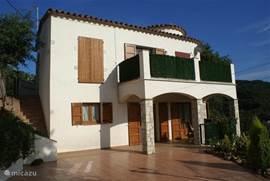 De villa in spaanse stijl met rondingen, luiken en toren gezien vanaf het terras.