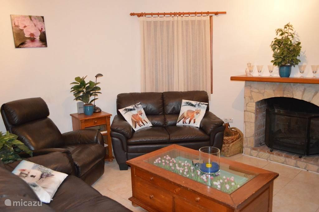 De woonkamer met nieuw lederen bankstel, relaxstoel en open haard.