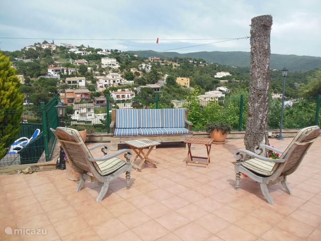 Gezellige zithoek met bank en stoelen op het terras