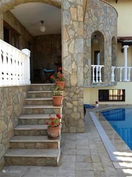 trap naar het zwembad en terras met ligstoelen