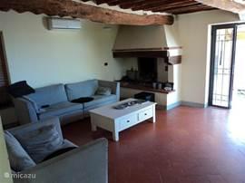 Ook de woonkamer is voorzien van een authentiek Toscaans balkenplafond. En een gezellige open haard. Alle kamers zijn voorzien van airconditioning