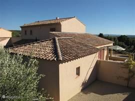 Achteraanzicht van de villa. Achtergebouw is de ruime garage. Daarvoor een van de terrassen met schitterend uitzicht.
