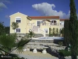 Vooraanzicht villa:   mooie tuin met wandelpaden, bankjes, fruit en palmbomen, en veel privacy. Huurprijs vanaf €48.= per week