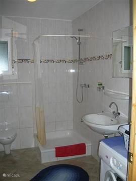Badkamer 1 met douche, wastafel, hangtoilet, en wasmachine, via hal naar de slaapkamers.