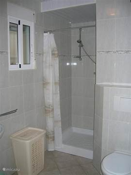 Badkamer 2 met douche, wastafel, en hangtoilet in verbinding met slaapkamer.