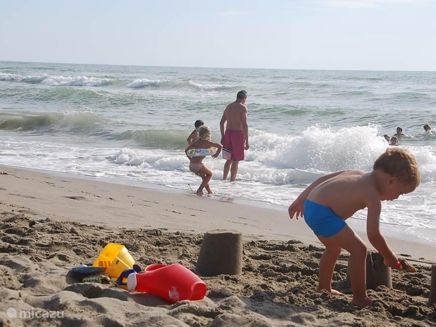 Op het zandstrand vermaken de kinderen zich uren, kastelen bouwen, kuilen graven, springen over de golven... dit is vakantie!