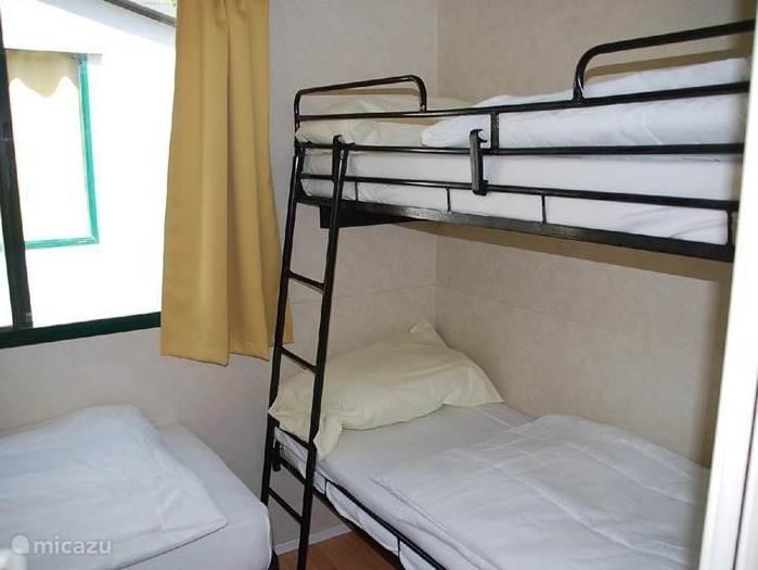 In de 2e slaapkamer staan drie bedden; een stapelbed, een eenpersoons bed en een kast. Op de bedden ligt een molton, eenpersoonsdekbed en een kussen.  Voor 50 euro toeslag per week kunt u ook kiezen voor een stacaravan met 3 slaapkamers. In het reserveringsformulier kunt u kiezen voor deze optie.