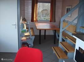 De doorkijk naar de eetkamer met lange tafel en twee banken