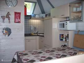 De gezellige open keuken met boven zit en open vide