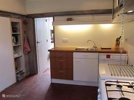 Keuken met gasfornuis en elektrische oven, magnetron, koelkast, afwasmachine en aanrecht. Geeft via gang toegang tot badkamer/toilet en tot trap naar slaapkamer 2