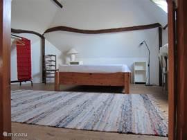 Slaapkamer 1 met traphekje en 2e directe toegang tot slaapkamer 2. Zeer ruim met een 2-persoonsbed, schrijftafel, kledingrek en kledingkast. Ruimte voor opklapbed en kinderbed.