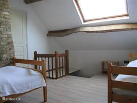 Slaapkamer 2 met twee 1-persoonsbedden. Toegang via trap vanaf begane grond en via deur tot slaapkamer 1. De trap is afsluitbaar voor kleine kinderen met een vergrendeld luik.