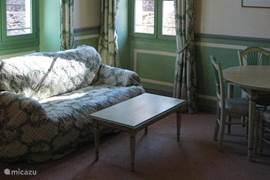 De ruime kamer met zit- en eetkamermeubilair. In de kamer bevindt zich tevens een 2-persoons opklapbed