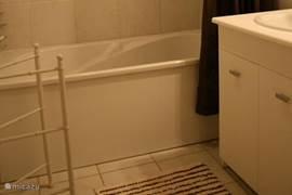 Badkamer met douche en bad.
