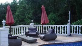 Loungeset bij zwembad met buitendouche.