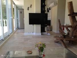 woonkamer appartement met achter de pilaar met tv de keuken