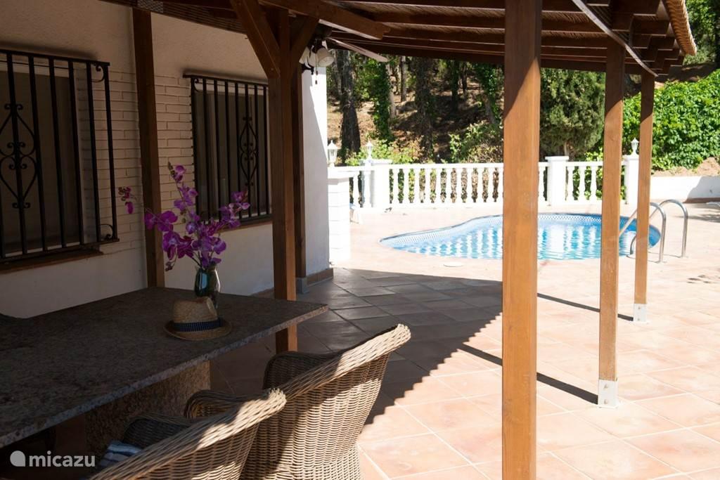 Voorzijde woning bij de entree. Overdekte gedeelte voor de keuken en naast het zwembad met granieten tafel(2x1m) waar je heerlijk kunt eten/bbq of een kaartje leggen.Grote stenen bbq staat rechts maar niet op foto