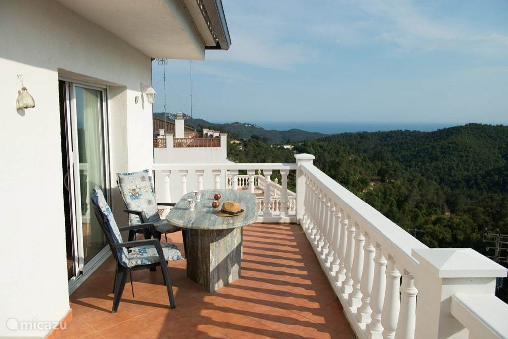 Balkon aan achterzijde woning, granieten tafel,stoelen en buitenverlichting. Van hieruit kijkt U over mooie beboste vallei en daarachter de zee.Heerlijke plek om te ontbijten of om 's avonds van de ruimte te genieten.