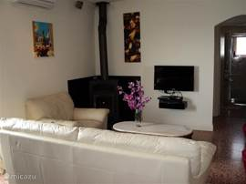 Woonkamer met lederen fauteuil/bank,houtkachel,airco,flatscreen full hd,blue ray speler en doorgang naar badkamer en de 3 slaapkamers