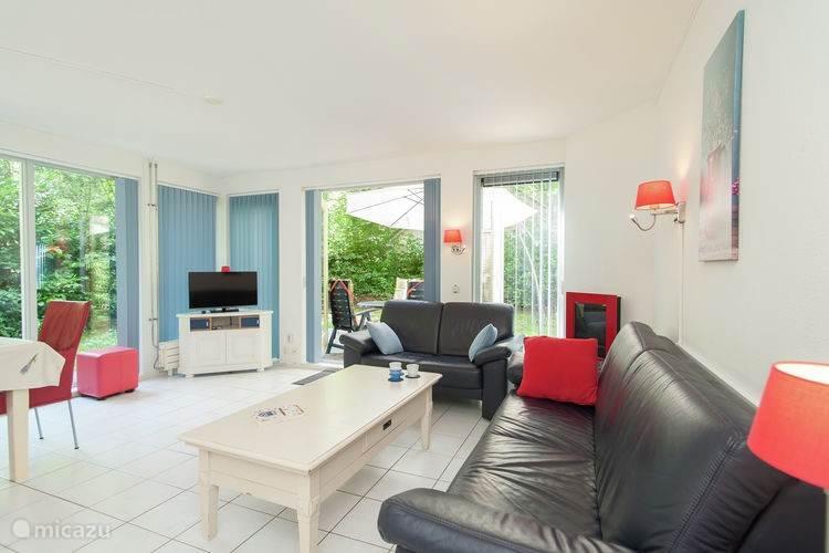 De woonkamer is voorzien van een sfeerhaard en TV.