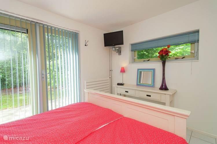 De slaapkamer op de benedenverdieping is voorzien van een televisie