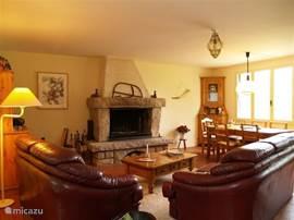 De woon/eetkamer (6x6)met een grote granieten schouw is o.a. voorzien van een knusse zithoek, een forse eettafel en een gezellig barretje.  Het grote terras is bereikbaar via de openslaande deuren.