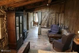 Het woongedeelte is van de keuken gescheiden door een wand van eikenhout en klei (colombage). 's Avonds is het heerlijk wegzakken in de riante fauteuils. Het knapperend houtvuur zorgt verder voor de gezellige sfeer. Ook in de winter kan deze moderne houtkachel de Residence aangenaam verwarmen.