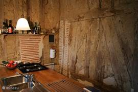 De keuken bestaat uit een eiland waardoor je aan twee kanten kunt werken. Terwijl je kookt kun je ondertussen van het uitzicht genieten. Het is een moderne en praktische keuken met een electrische oven, een ingebouwde koelkast en een vierpits gasstel.
